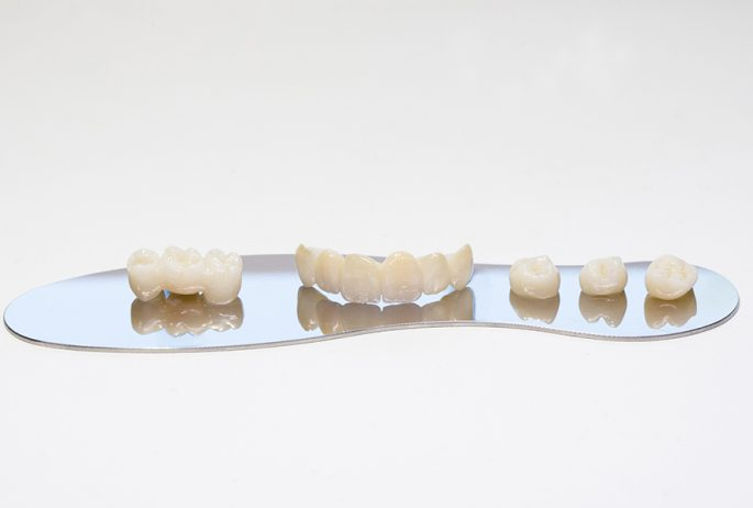 Ceramic zirconium in final version. Metal Free Ceramic Dental Crowns. Zirconium tooth crown. Isolate on background. Aesthetic restoration of tooth loss.